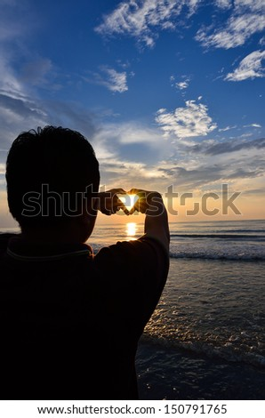 Silhouette of man doing heart shape with sunrise in the middle and beach - stock photo