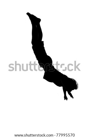 silhouette of man doing somersault - stock photo