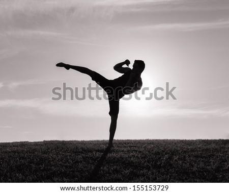 Silhouette of man exercising thai boxing - stock photo