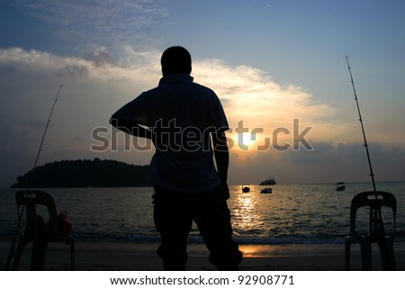 Silhouette of man fishing by the beach. - stock photo