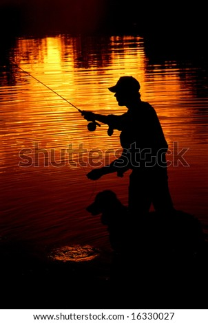 Silhouette of Man fly fishing with his dog - stock photo