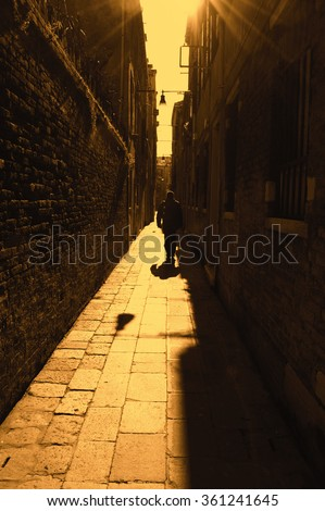 Silhouette of  man going on narrow street in shining sun rays. (Venice, Italy) A game of light and shadow. Light spots. Toned photo. - stock photo