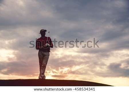 silhouette of man golfer with golf club at sunset - stock photo