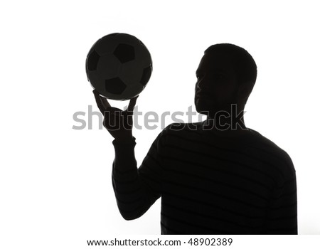 Silhouette of man holding ball in air, isolated on white background. - stock photo