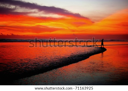 Silhouette of man in distance walking on beach at sunset, Bali. - stock photo