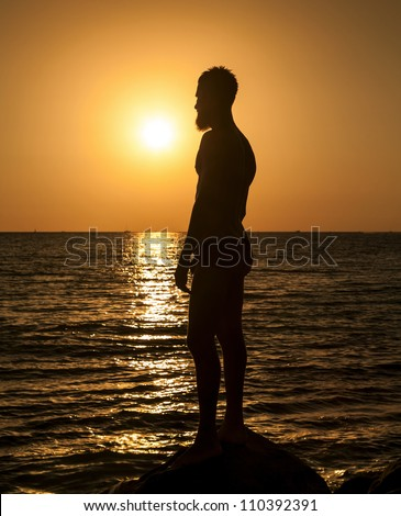 Silhouette of man in the beautiful sunset on the ocean - stock photo