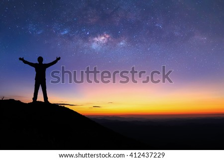 Silhouette of man is standing on top of mountain and spreading hand next to the milky way before sunrise. - stock photo
