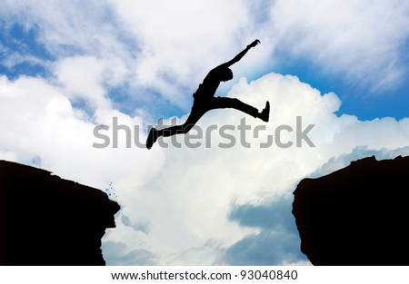 Silhouette of man jumping cliff with cloudy sky - stock photo