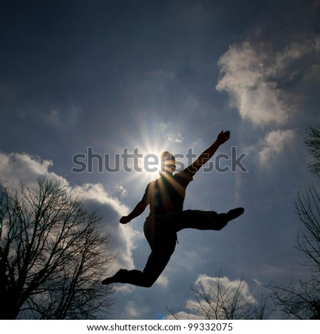 silhouette of man jumping in sky - stock photo
