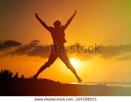 Silhouette of man jumping on sunset beach