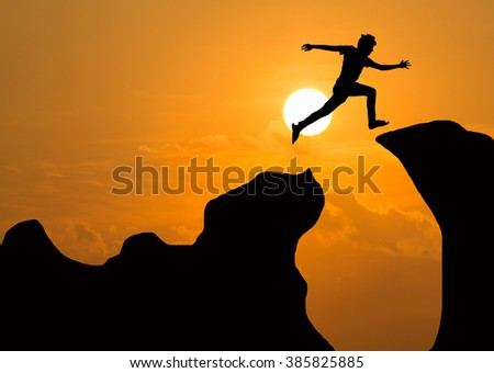 Silhouette of man jumping over cliff on sunset background