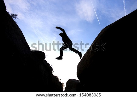 silhouette of man leaping between rocks against blue sky - stock photo