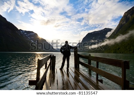 Silhouette of man looking on lake - stock photo
