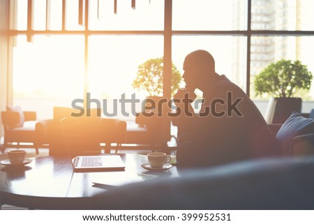 Silhouette of man managing director is thinking how to prevent the company's crisis,while is sitting with net-book in cafe. Male financier in watching world news on laptop computer during coffee break - stock photo