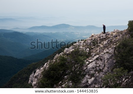 Silhouette of man on edge of a cliff - stock photo