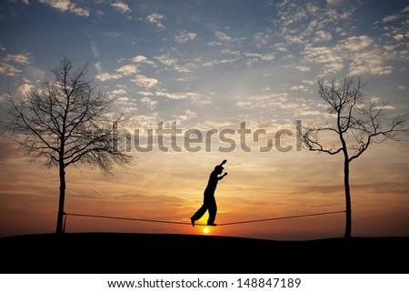 silhouette of man on slackline in sunset - stock photo