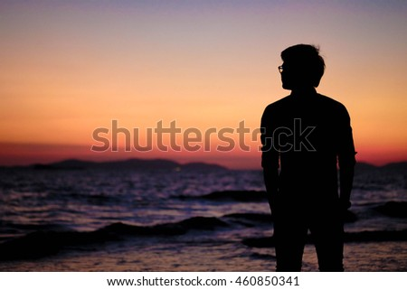 Silhouette of man on the beach during colorful sunset