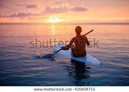 Silhouette of man paddling on paddle board at sunset. Watersport near the beach on sunset - stock photo