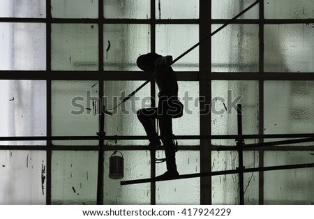 Silhouette of man painting on green glass window wall with paint roller