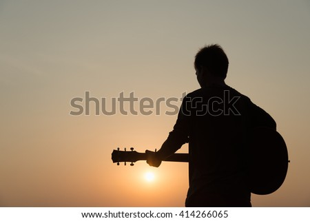 silhouette of man playing guitar at sunset - stock photo
