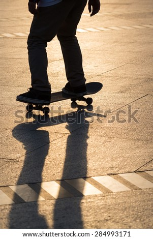 Silhouette of man playing skateboard in park - stock photo