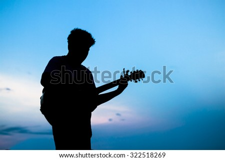 Silhouette of man playing the guitar beside sea at sunset