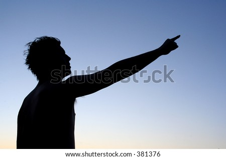 Silhouette of man pointing at something far away