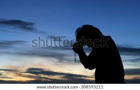 Silhouette of man praying  - stock photo