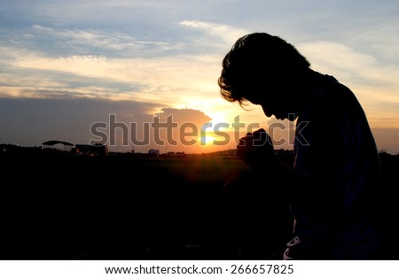 Silhouette of man praying over beautiful sunset background - stock photo
