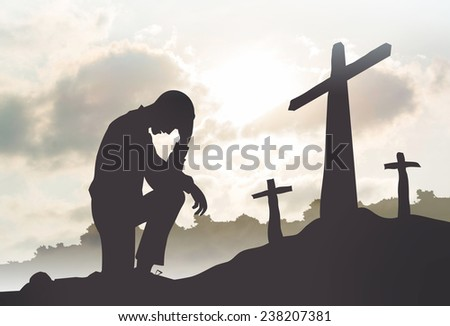 Silhouette of man praying to a cross with heavenly cloudscape sunset concept for religion - stock photo