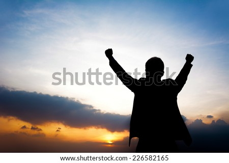Silhouette of man raising his arms - success, winning & accomplished concept - stock photo