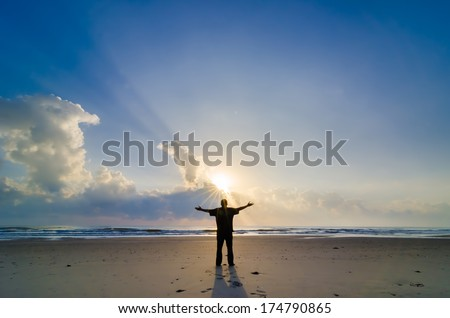 Silhouette of Man Raising His Hands or Open arms when sunrise - stock photo