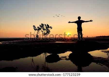 Silhouette of Man Raising His Hands or Open arms when sunset - stock photo