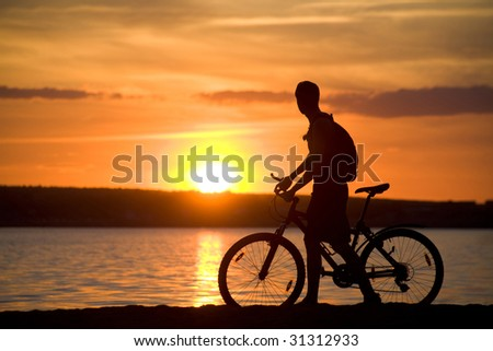 Silhouette of man riding bicycle with beautiful lake near by at sunset - stock photo