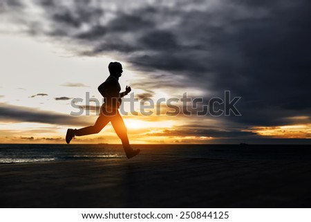 Silhouette of man running towards gold sun at cloudy dark sky background
