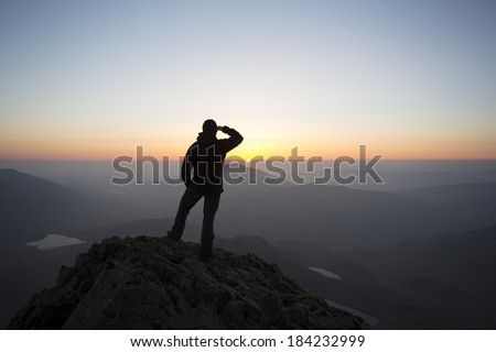 silhouette of man saluting to the early morning sunrise from a mountain top, crib goch, snowdon