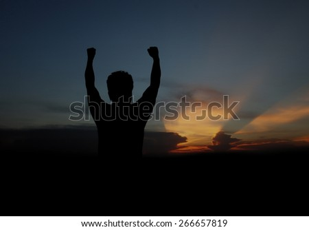 Silhouette of man show hand on sunset background - stock photo