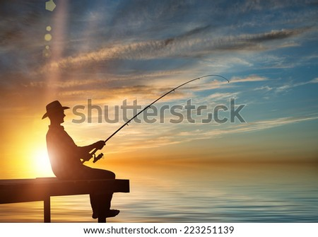 Silhouette of man sitting at bridge and fishing - stock photo