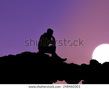 Silhouette of man sitting at sunset - stock photo