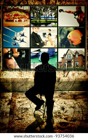 Silhouette of man sitting in front of video wall watching multimedia screens. - stock photo