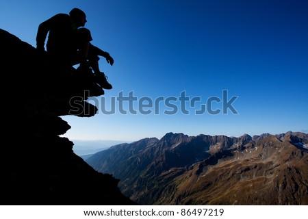 Silhouette of man sitting on rock above mountain range - stock photo