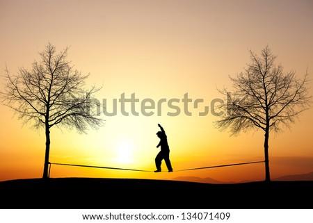 silhouette of man slacklining in sunset - stock photo