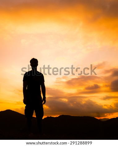 Silhouette of man standing a lone on top of mountain with orange twilight in the dark evening light from the back.