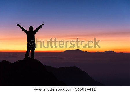 silhouette of man standing and spread hand on the top of mountain to enjoy colourful sky. - stock photo