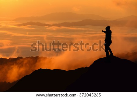 Silhouette of man standing and thump up on the top of mountain.