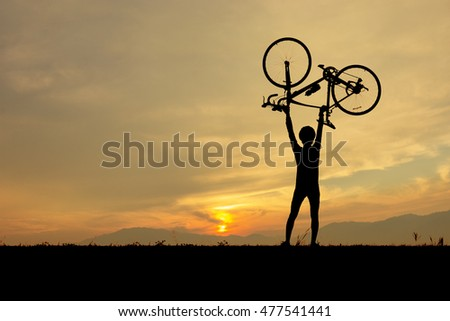 Silhouette of man standing, Him lifting up bike on meadow and looking at the sky in sunset time.