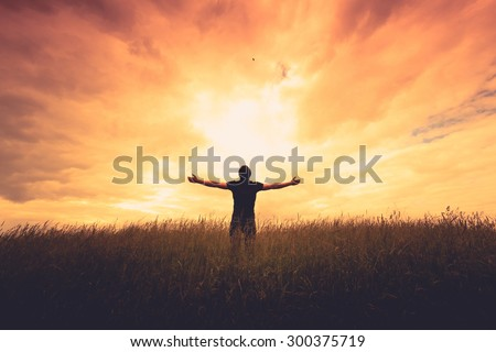 silhouette of man standing in a field at sunset - stock photo