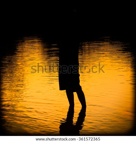 Silhouette of man standing in the water - stock photo