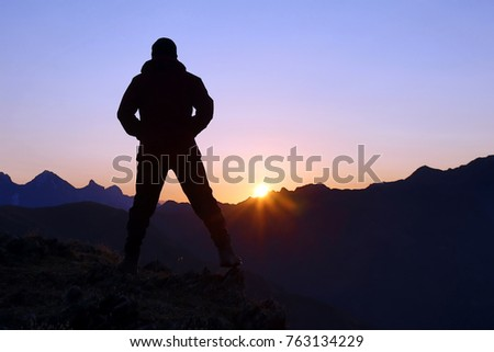 silhouette of man standing on the mountain face to sunrise