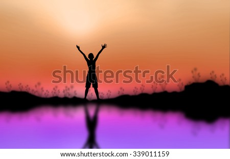 Silhouette of man standing on the mountain raise exposure. - stock photo